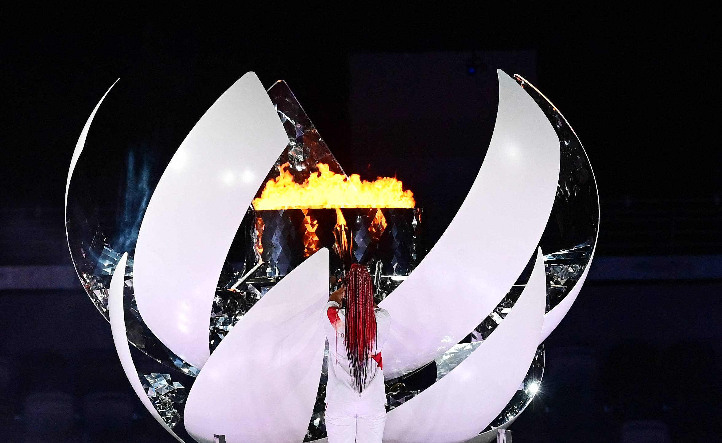 Tennis start Naomi Osaka lights the flame of hope in the Olympic Cauldron during the opening ceremony. | AFP-JIJI