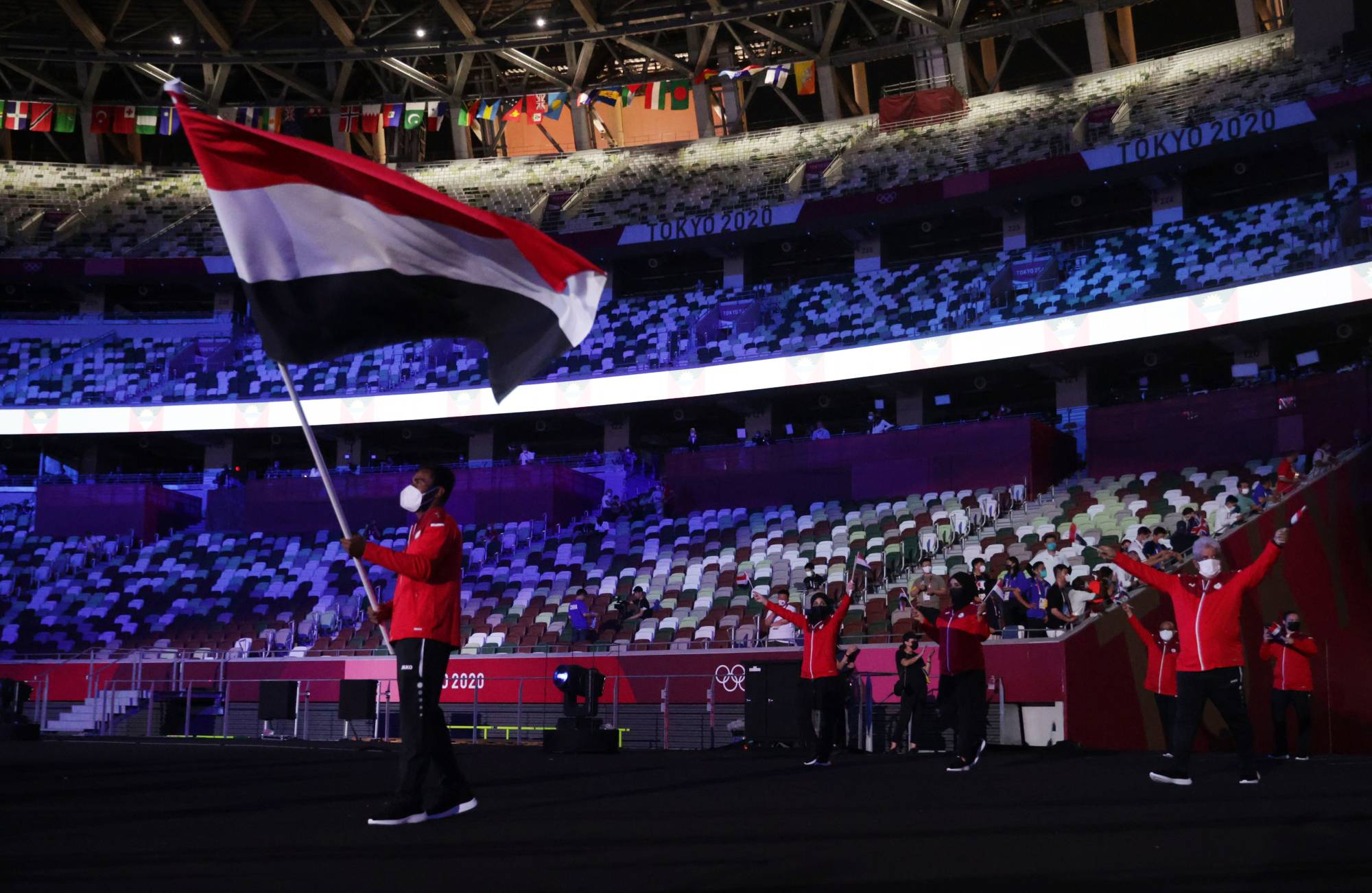 Flagbearer Yasameen Al Raimi of Yemen lead his contingent in the athletes parade during the Tokyo Olympics opening ceremony Friday. Countries were listed by their Japanese pronunciation. For example, Yemen — 'Iemen' in Japanese — came near the front, not the back. | REUTERS