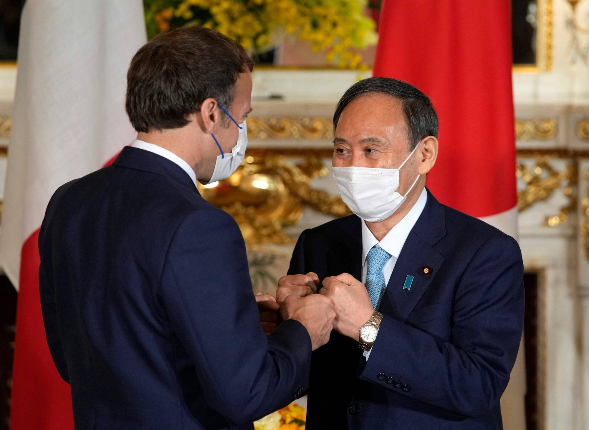Prime Minister Yoshihide Suga greets French President Emmanuel Macron ahead of their meeting at the Akasaka State Guest House in Tokyo on Saturday.  | POOL / VIA AFP-JIJI