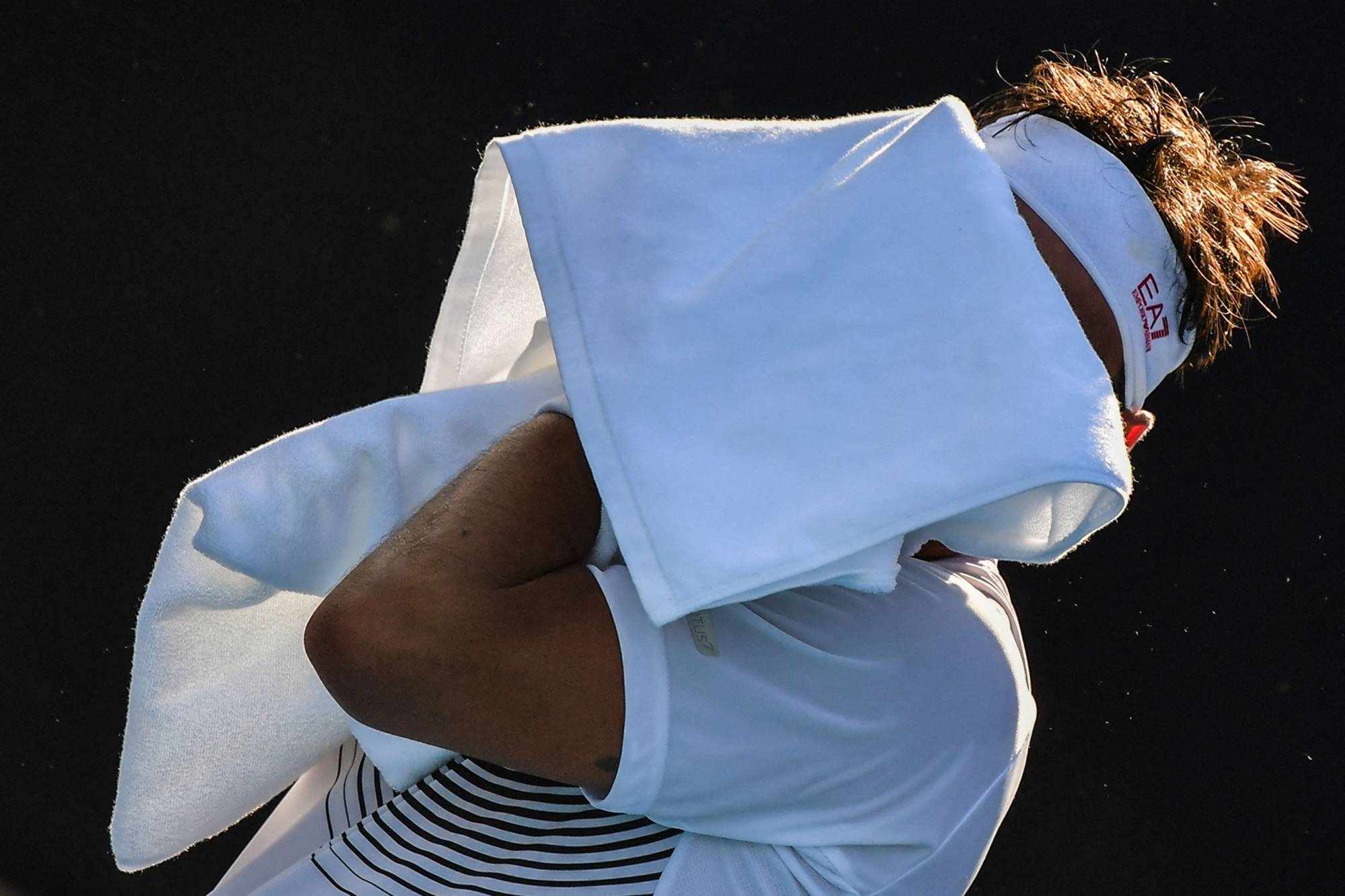 Italy's Fabio Fognini wipes his face with a towel during his first-round match with Japan's Yuichi Sugita on Saturday in Tokyo. | AFP-JIJI