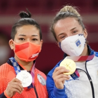 Women's under-48 kg silver medalist Yuna Tonaki (left) and poses with gold medalist Distria Krasniqi during the medal ceremony on Saturday. | KYODO