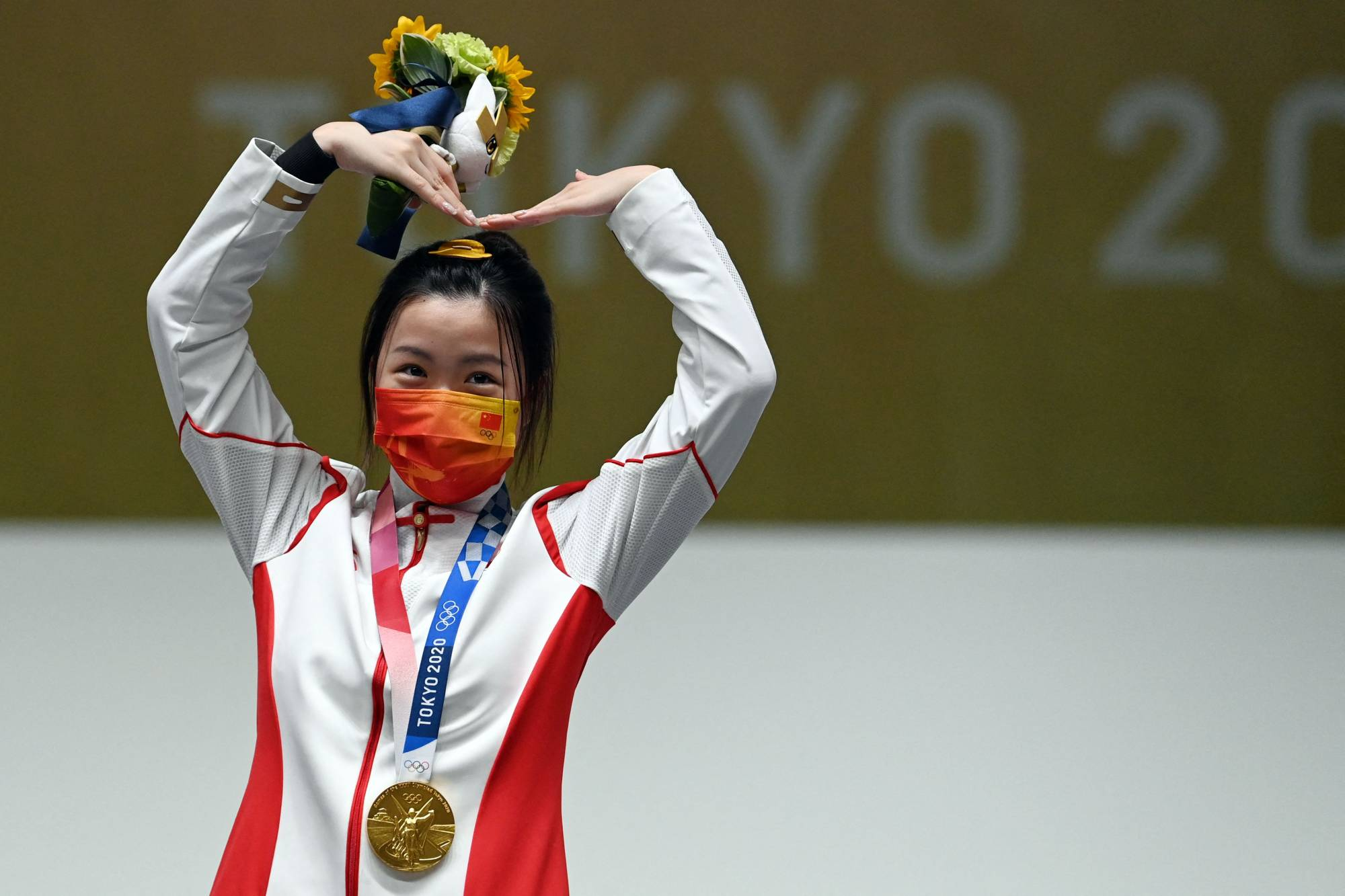 Gold medal winner China's Yang Qian celebrates on the podium after winning the women's 10 meter air rifle final on the first day of the Tokyo 2020 Games.  | AFP-JIJI