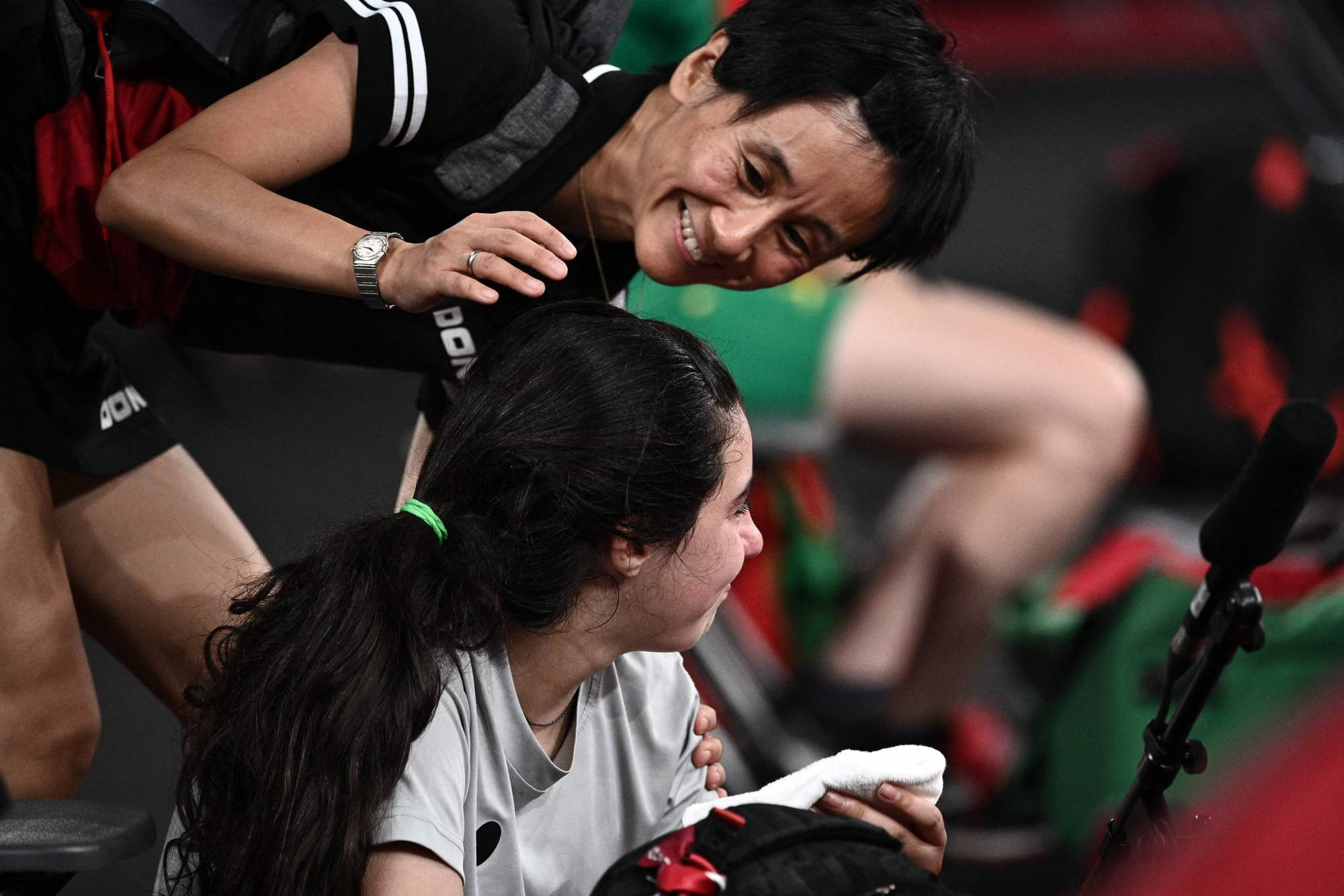 Syria's Hend Zaza is comforted by Austria's Liu Jia after being defeated 4-0 during their women's singles preliminary round table tennis match at the Tokyo Metropolitan Gymnasium on Saturday. | AFP-JIJI