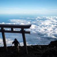A man reaches the summit of Mount Fuji, with a sea of clouds seen below, on July 18.    AFP-JIJI