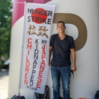 French resident Vincent Fichot stands with his banner where he has been on a hunger strike near the National Stadium in Tokyo on July 21. | REUTERS