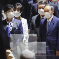 Tokyo Gov. Yuriko Koike and Prime Minister Yoshihide Suga attend the opening ceremony of the Tokyo Olympics at the National Stadium on Friday. The two met on Sunday to discuss the Olympics and COVID-19 measures.   KYODO