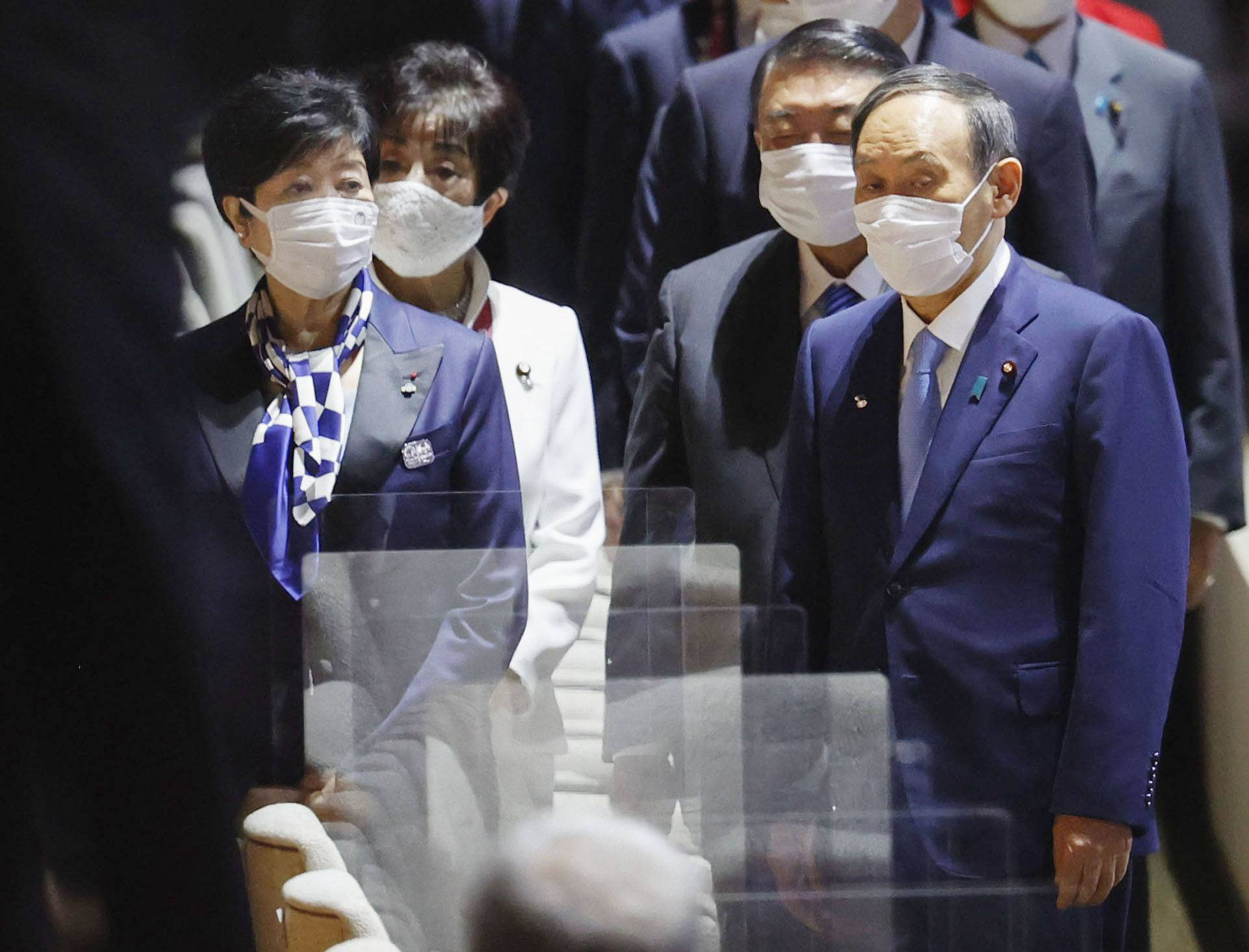 Tokyo Gov. Yuriko Koike and Prime Minister Yoshihide Suga attend the opening ceremony of the Tokyo Olympics at the National Stadium on Friday. The two met on Sunday to discuss the Olympics and COVID-19 measures. | KYODO