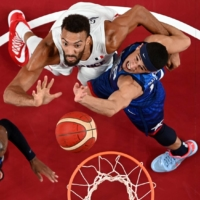 Rudy Gobert of France in action at the rim with Damian Lillard and Devin Booker of the United States at Saitama Super Arena on Sunday | REUTERS