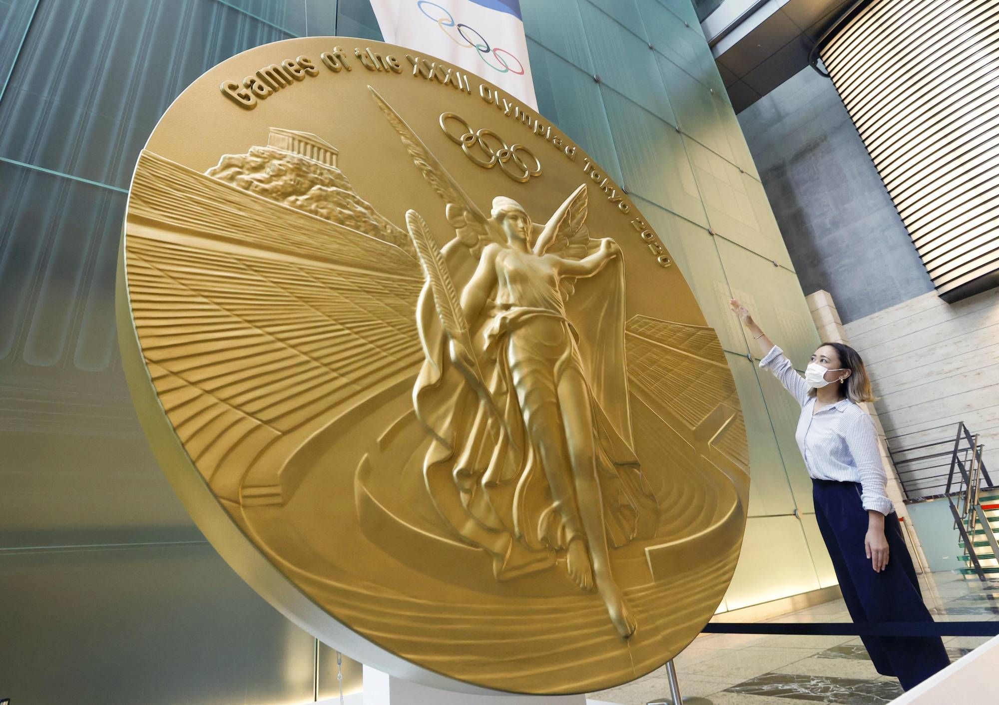 Golden opportunity: A woman stands in front of a 2.5-meter tall replica of a Tokyo Olympics gold medal at Nihonbashi Mitsui Tower in Tokyo. | KYODO