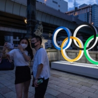 A couple poses in front of the Olympic Rings in Tokyo's Nihonbashi district on Saturday.   AFP-JIJI