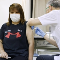 A woman is vaccinated in Fukuoka Prefecture on July 20. | KYODO