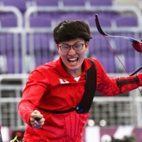 Hiroki Muto of Japan celebrates after winning bronze for his team in the men's archery team event.  | REUTERS