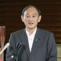 Prime Minister Yoshihide Suga tells reporters Monday at the Prime Minister's Office that the government has decided to give up on appealing a Hiroshima High Court ruling which recognized 84 people as hibakusha.  | KYODO