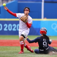 Japan's Hitomi Kawabata makes a play as Janie Reed of the United States slides during their softball game in Yokohama on Monday. The U.S. beat Japan 2-1. | REUTERS
