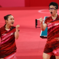 Japan's Mima Ito and Jun Mizutani pump their fists during the mixed doubles Olympic gold-medal match on Monday in Tokyo. | REUTERS