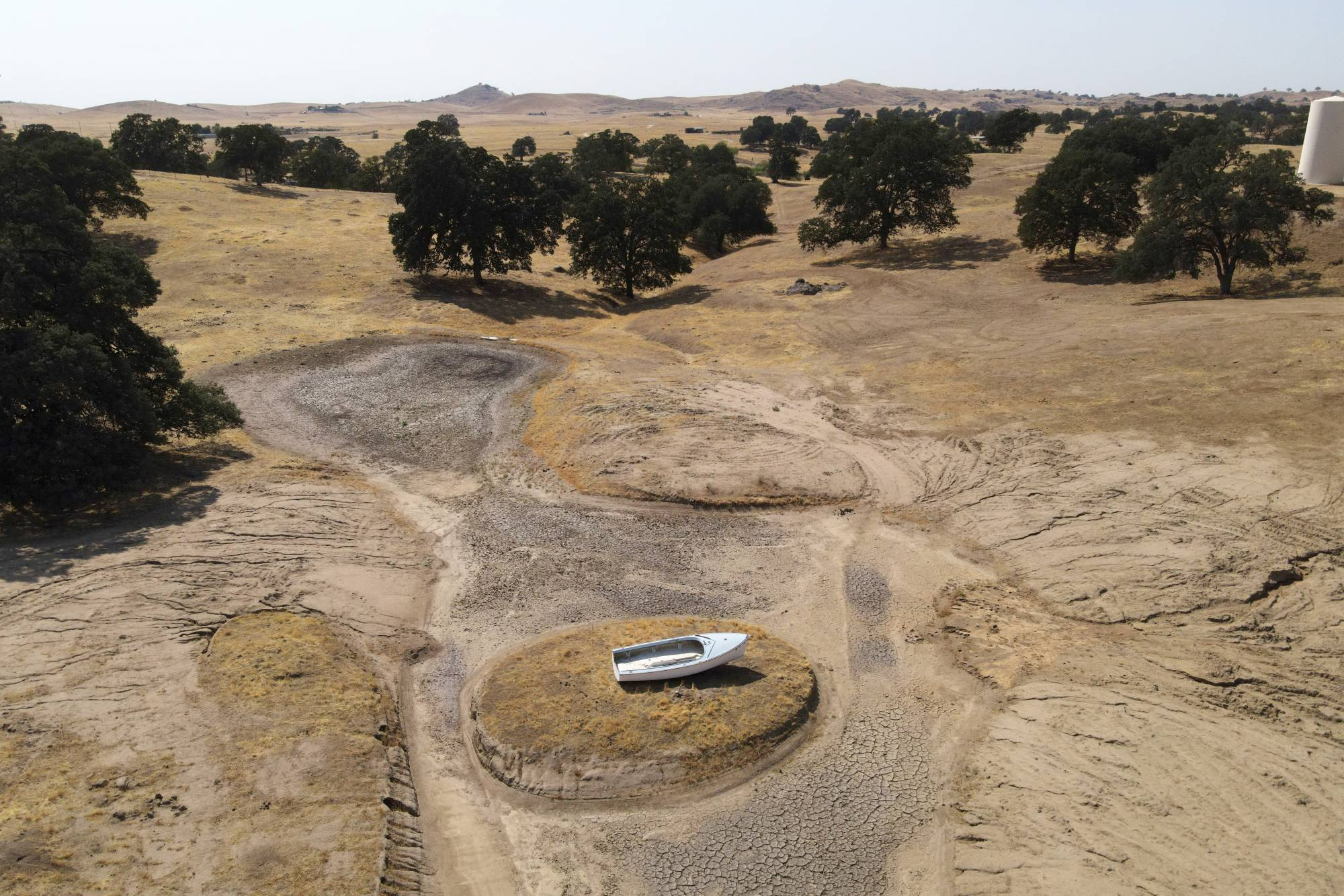 A lone boat sits perched on a mound near Hensley Lake as soaring temperatures and drought continue to affect livestock and water supplies in Madera, California, on July 14.   REUTERS