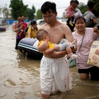 A man holding a baby wades through a flooded road following heavy rainfall in Zhengzhou, Henan province, China, on Thursday.   REUTERS