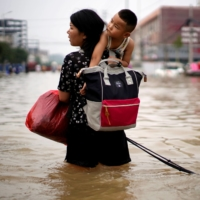 A woman carrying a child and belongings wades through floodwaters following heavy rainfall in Zhengzhou, Henan province, China, on Friday.   REUTERS