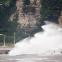 Waves crash against a seawall amid stormy conditions at Tsurigasaki Surfing Beach in Tokyo on Monday.  | REUTERS