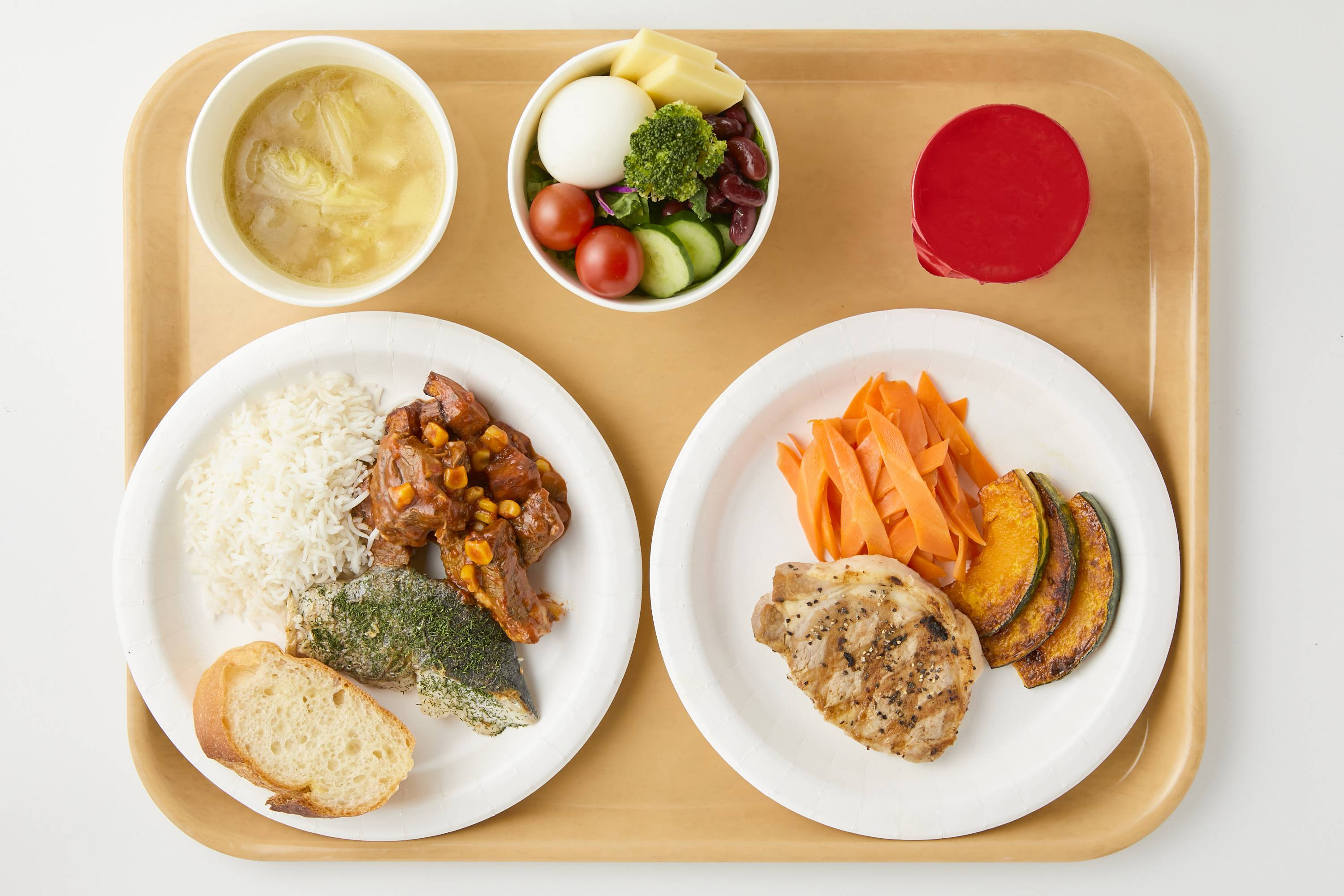A sample of dishes served in the main dining hall at the athletes' village: braised beef and vegetables, sauteed cod with herbs, basmati rice, baguette (front left), grilled pork, grilled vegetables (front right), cabbage soup (back left), mixed salad (back center) and yogurt. | TOKYO 2020 / VIA KYODO
