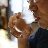A customer drinks sake at a bar in Tokyo on June 21, following a slight easing of COVID-19 restrictions.   KYODO