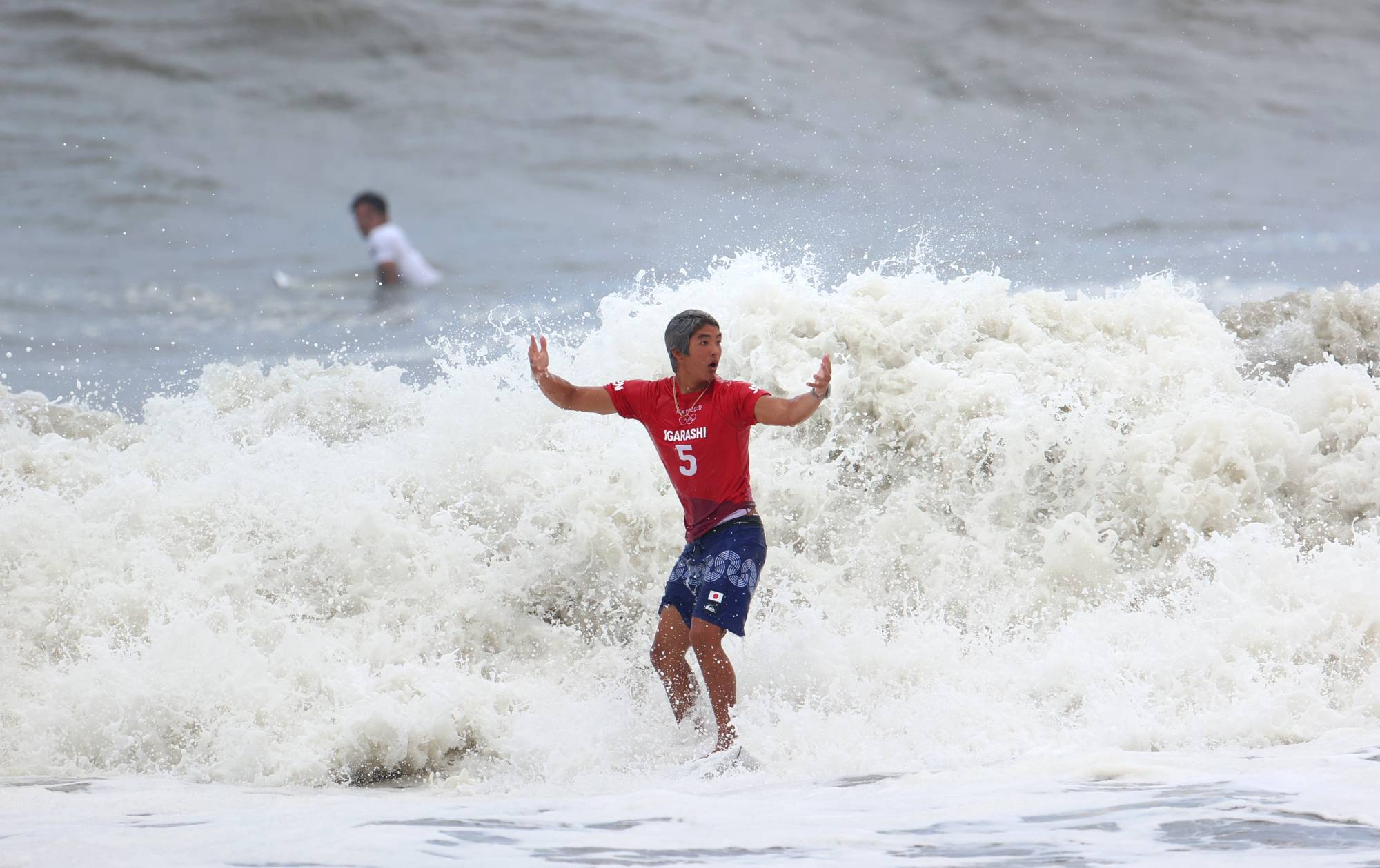 Kanoa Igarashi of Japan celebrates with his opponent, Gabriel Medina of Brazil, in the background.   REUTERS