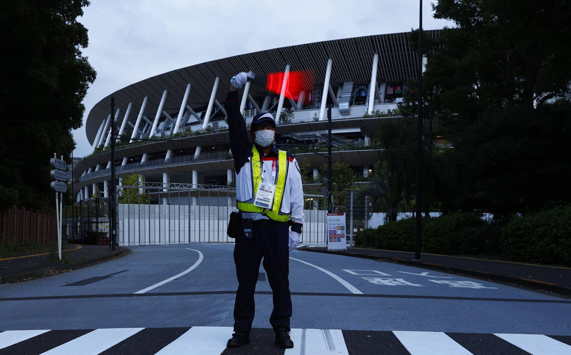 A security guard stands outside the National Stadium to halt the traffic around it earlier this month.   KYODO