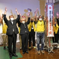 Akita Prefecture officials on Tuesday celebrate the UNESCO World Heritage Committee decision to register a set of ruins from the ancient Jomon Period as a World Heritage cultural property. | KYODO