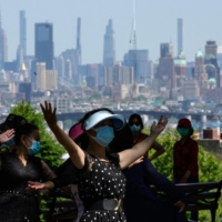 Women dance in a park in New York in May.  | AFP-JIJI
