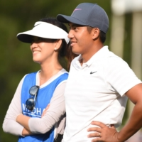 C.T. Pan (right) and wife and caddie, Michelle Lin, wait on the 18th green at the 2018 Wyndham Championship.