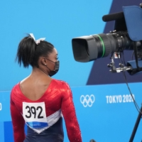 Simone Biles of the United States walks near a television camera during the women's team gymnastics final at the Tokyo Games on Tuesday.  | DOUG MILLS / THE NEW YORK TIMES