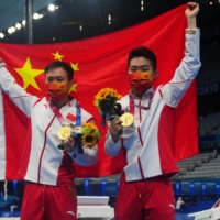 China's Wang Zongyuan and Xie Siyi pose with their gold medals after winning the men's synchronized 3-meter springboard diving final.  | REUTERS