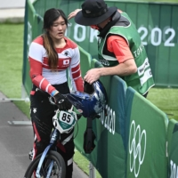 Japan's Sae Hatakeyama is comforted by her coach after falling in the cycling BMX racing women's quarterfinals at Ariake Urban Sports Park on Thursday.