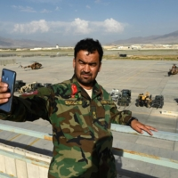 An Afghan National Army soldier takes a selfie inside Bagram Air Base near Kabul after all U.S. and NATO troops left, on July 5.  Russia has reportedly offered the U.S. the use of Russian military bases in Central Asia.  | AFP-JIJI
