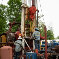 Workers operate a drill rig at a gas well plugging site in Roan County, West Virginia. | REUTERS