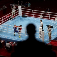 A spectator watches a fight boxing bout at the 2020 Tokyo Games on July 28. | UESLEI MARCELINO / REUTERS