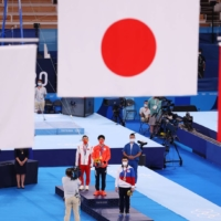 (From left) Silver medalist Ruoteng Xiao of Team China, gold medalist Daiki Hashimoto of Team Japan and bronze medalist Nikita Nagornyy of Team ROC stand on the podium during the medal ceremony following the Men's All-Around Final on day five of the Olympic Games at Ariake Gymnastics Center on Wednesday. | GETTY IMAGES / VIA BLOOMBERG