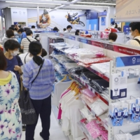People shop at an official Tokyo 2020 merchandise store in Tokyo's Shinjuku district on Monday. | KYODO