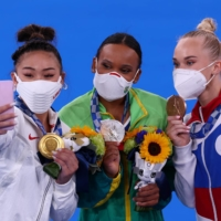 Gold medalist Sunisa Lee of the United States takes a selfie with silver medalist Rebeca Andrade of Brazil  and bronze medalist Angelina Melnikova of the Russian Olympic Committee. | REUTERS