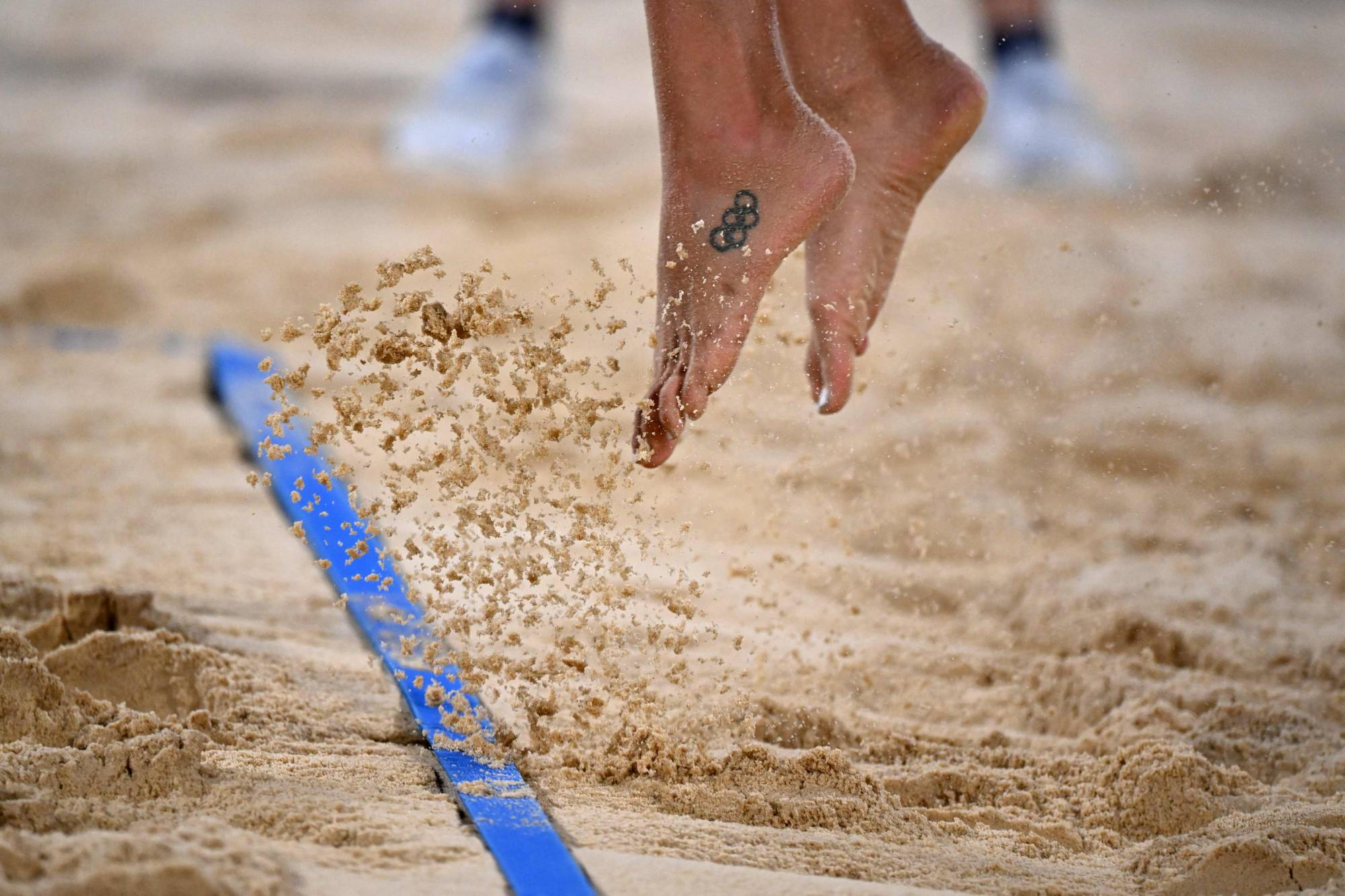 A player takes to flight during the women's preliminary beach volleyball match between Australia and Italy | AFP-JIJI