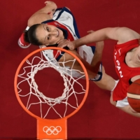 Diana Taurasi of the U.S. (left) and Japan's Maki Takada jump for the ball in their group match at Saitama Super Arena on Friday.  | AFP-JIJI