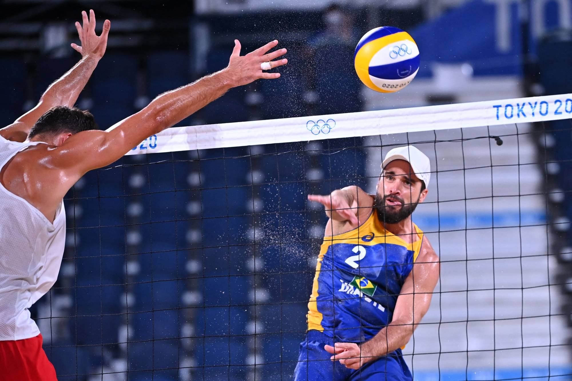 Brazil's Bruno Oscar Schmidt (right) spikes the ball as Poland's Michal Bryl defends in the men's preliminary beach volleyball pool match. | AFP-JIJI