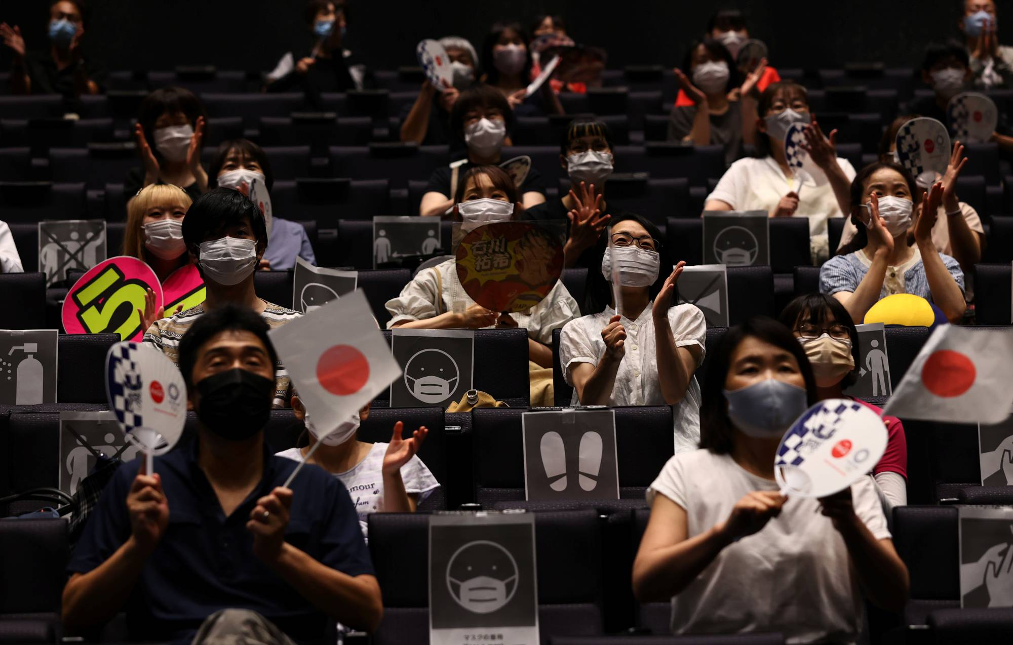 People watch a live broadcast of a volleyball match between Japan and Poland on a large screen during a public viewing event for the Tokyo Olympics at a theater in Takasaki, Gunma Prefecture, on Friday.   REUTERS