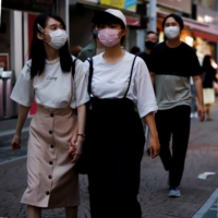 Women walk by a shop selling masks in Tokyo on Friday.