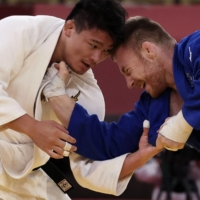 Japan's Shoichiro Mukai and France's Axel Clerget compete in the judo mixed team gold medal match at Tokyo's Nippon Budokan on Saturday.  | AFP-JIJI