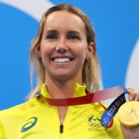 Emma McKeon of Australia poses on the podium with her gold medal in the women's 100-meter freestyle.  | REUTERS