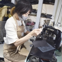 Minako Wada works on a deerskin leather product in the atelier at the apparel shop Inswirl, in Nagano on June 9.   KYODO