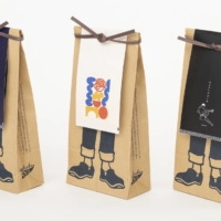 The paper packaging for Anything Co. Ltd.'s maekake, featuring a label shaped as an apron, was created by Japanese design unit Nosigner. | HIROYUKI HARA
