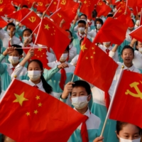Performers wave national and party flags as they rehearse before an event marking the 100th founding anniversary of the Communist Party of China, at Tiananmen Square in Beijing on Thursday.  | REUTERS