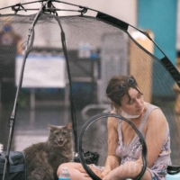 A woman and her cat rest inside a tent at the Oregon Convention Center cooling station in Portland, Oregon, on Wednesday. | AFP-JIJI